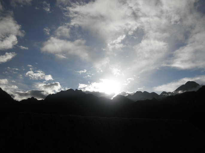 The sun peeking out over the mountain.